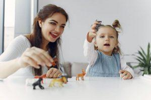 Niña jugando con figuritas de animales